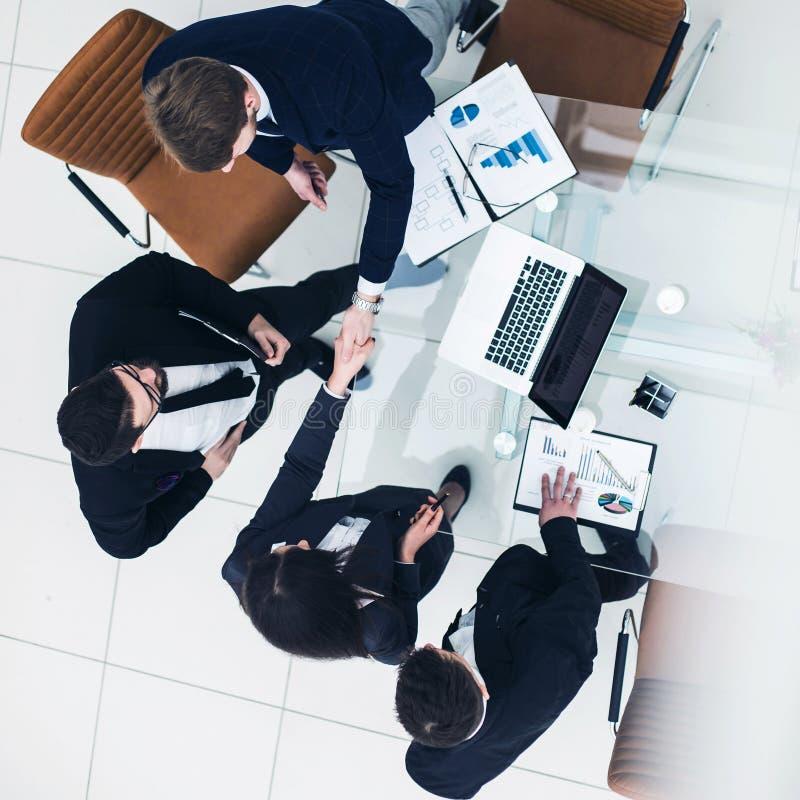 Soci commerciali affidabili della stretta di mano dopo la discussione sul contratto finanziario nell'ufficio immagini stock libere da diritti