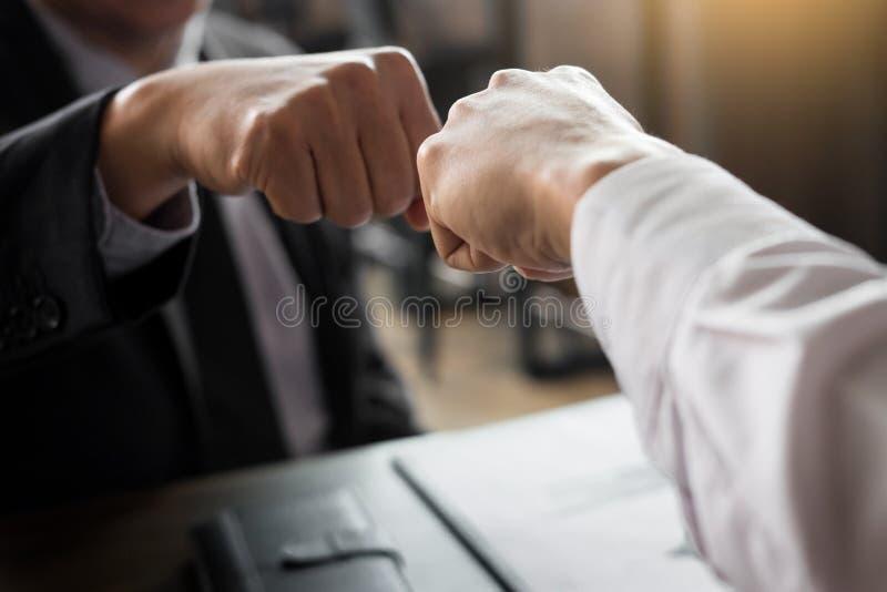 Soci commerciali che danno l'urto del pugno all'inizio di saluto di impegno immagine stock