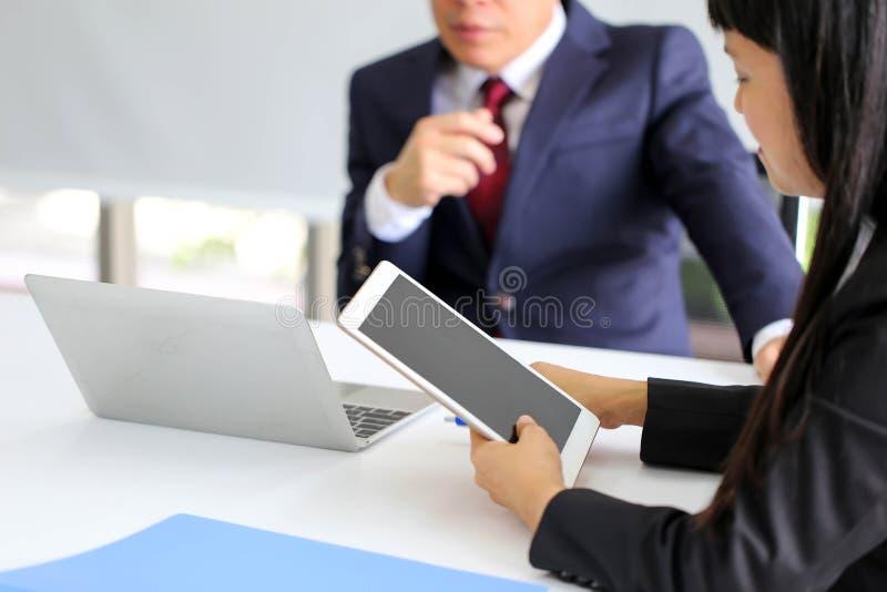 Soci commerciali che discutono i documenti e le idee alla riunione, anale fotografia stock