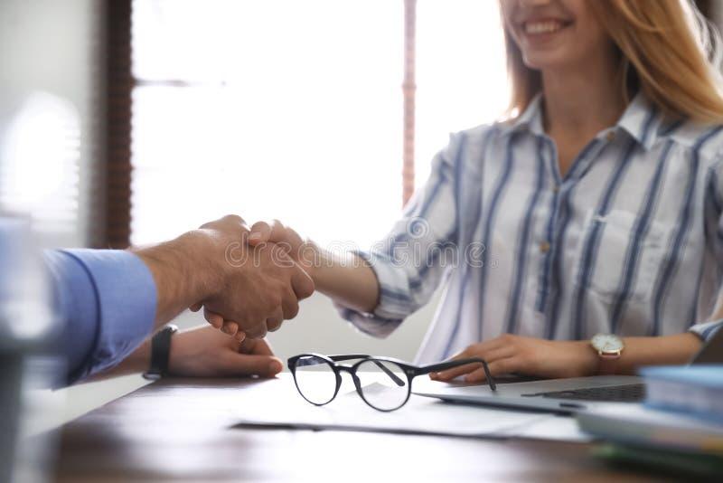 Soci commerciali che stringono le mani alla tavola dopo la riunione nell'ufficio immagine stock