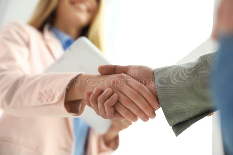 Soci commerciali che stringono le mani dopo la riunione fotografia stock
