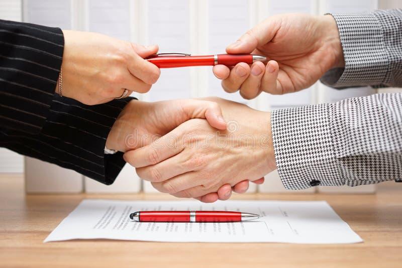 Soci commerciali che stringono le mani e che scambiano penna dopo il finishe fotografia stock