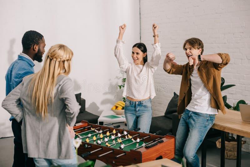 soci commerciali felici che celebrano vittoria nel calcio-balilla con le armi su ed i pollici giù i gesti davanti a fotografia stock
