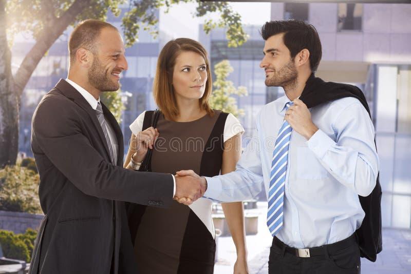 Soci di affari che stringono le mani sulla via fotografia stock