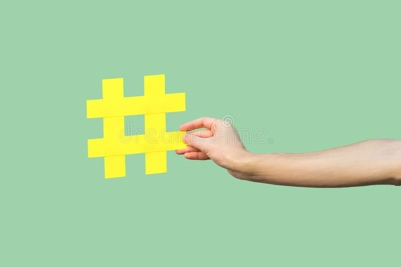 Sociaal media concept, close-upportret die van hand het grote grote gele teken van de knoeiboelmarkering houden stock fotografie