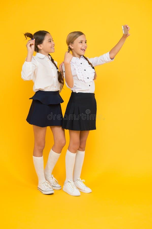Sociaal netwerk gelukkige vrienden met smartphone de jonge geitjes maken selfie foto, vriendschap kleine meisjes in eenvormige sc royalty-vrije stock fotografie