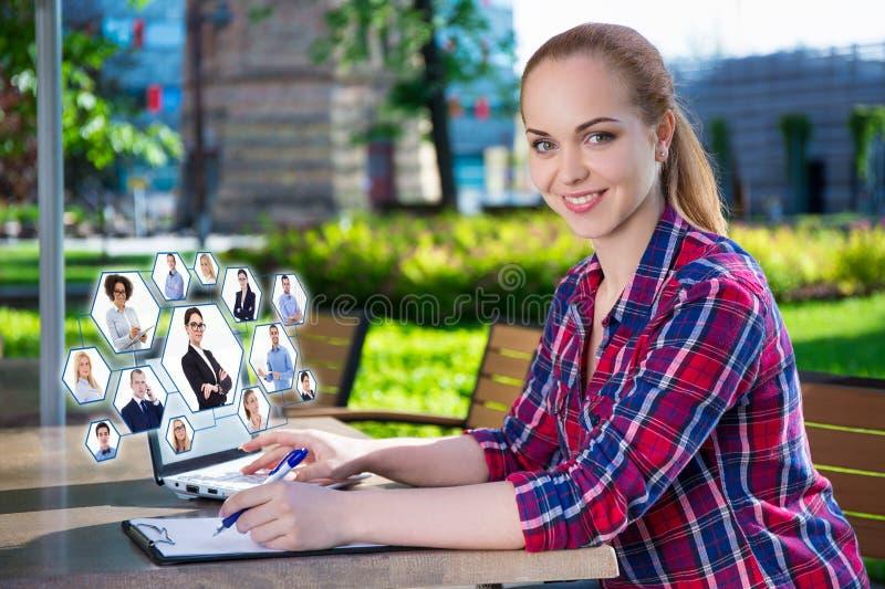 Sociaal netwerkconcept - mooie tiener die laptop binnen met behulp van stock foto's