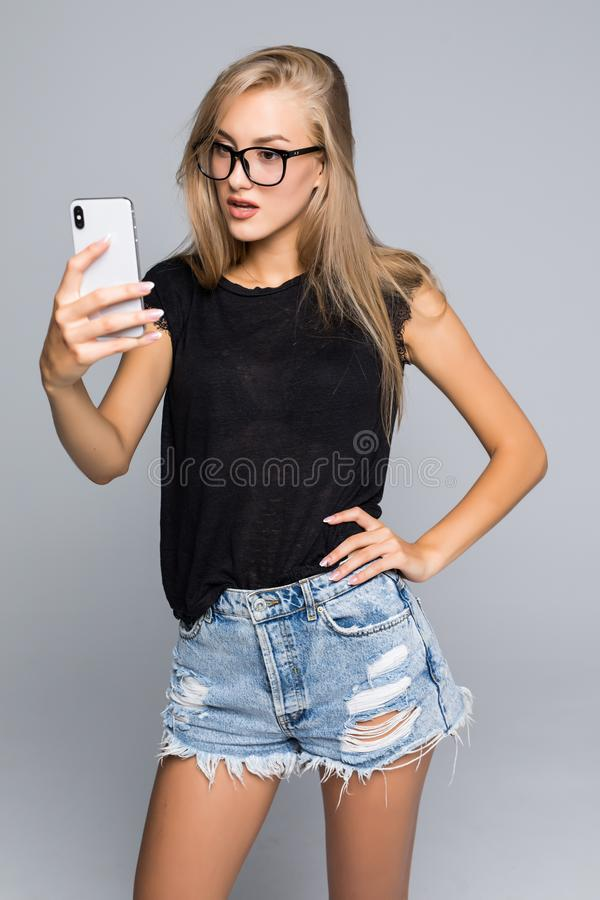 Sociable beautiful woman taking selfie or speaking on video call using cell phone over gray background. Sociable beautiful woman make selfie or speaking on video royalty free stock image