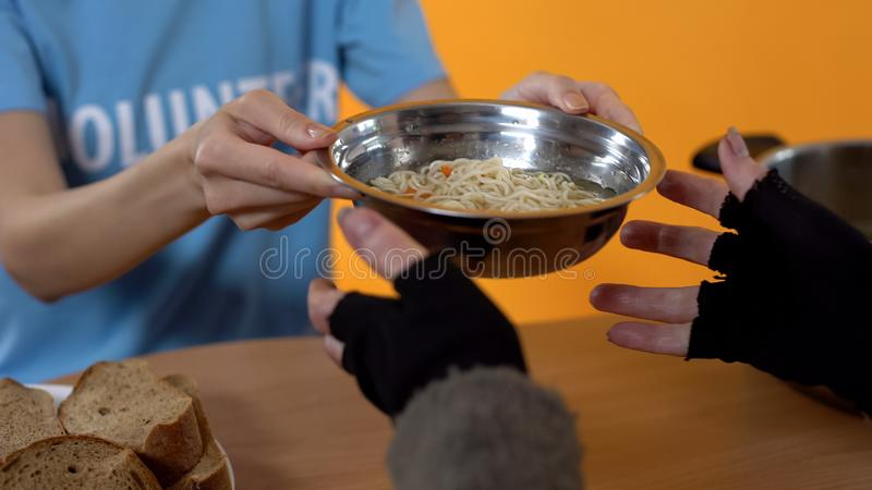 Social activist giving soup bowl homeless female, charity food in shelter, help. Stock photo royalty free stock photos