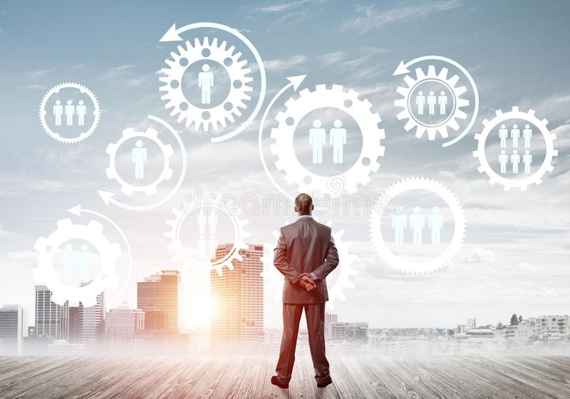 Social connection concept drawn on screen as symbol for teamwork and cooperation. Back view of businessman looking at modern cityscape and gear connection idea stock image
