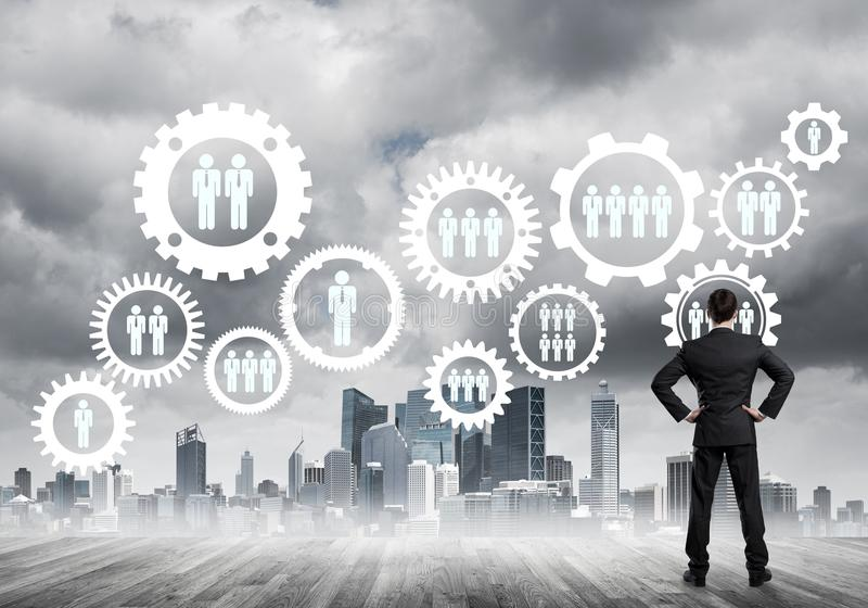 Social connection concept drawn on screen as symbol for teamwork and cooperation. Back view of businessman looking at modern cityscape and gear connection idea stock photos