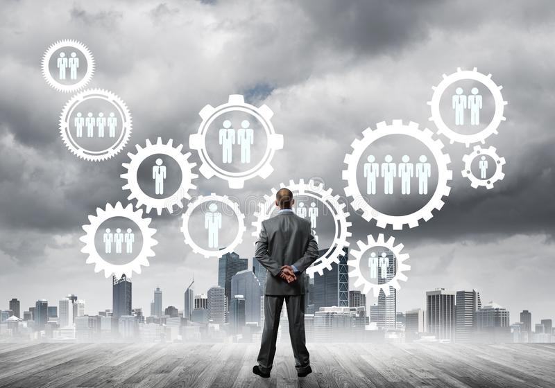 Social connection concept drawn on screen as symbol for teamwork and cooperation. Back view of businessman looking at modern cityscape and gear connection idea royalty free stock photos