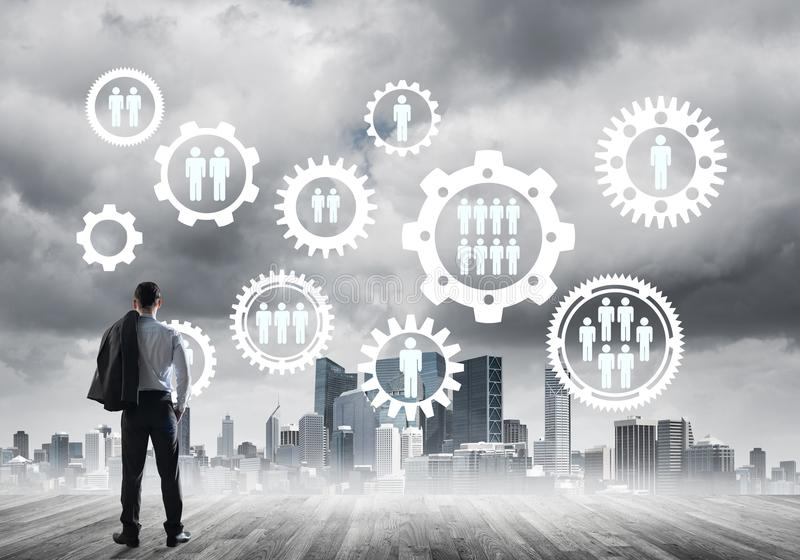 Social connection concept drawn on screen as symbol for teamwork and cooperation. Back view of businessman looking at modern cityscape and gear connection idea stock images