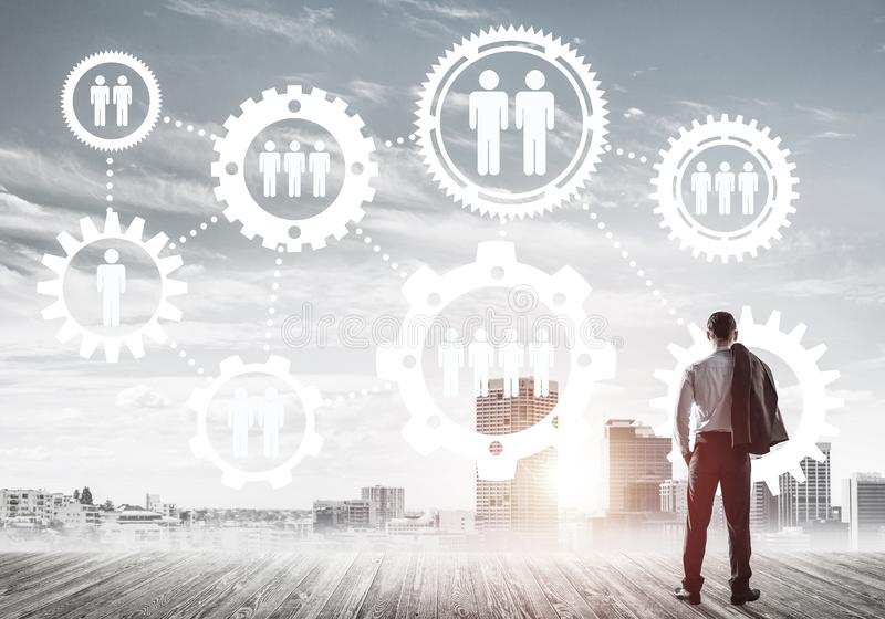 Social connection concept drawn on screen as symbol for teamwork and cooperation. Back view of businessman looking at modern cityscape and gear connection idea royalty free stock photography