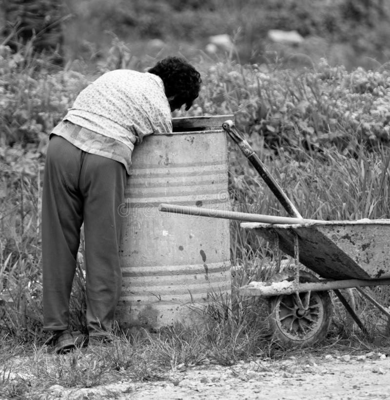 Social crisis of a woman digging rubbish bin for food. MALAYSIA, JOHOR - DECEMBER 2010: An unidentified woman seeks food from a metal trash container. Absolute royalty free stock photo