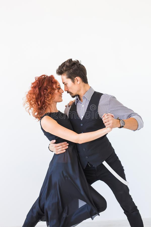 Social dance, bachata, kizomba, tango, salsa, people concept - Young couple dancing over white background royalty free stock photo