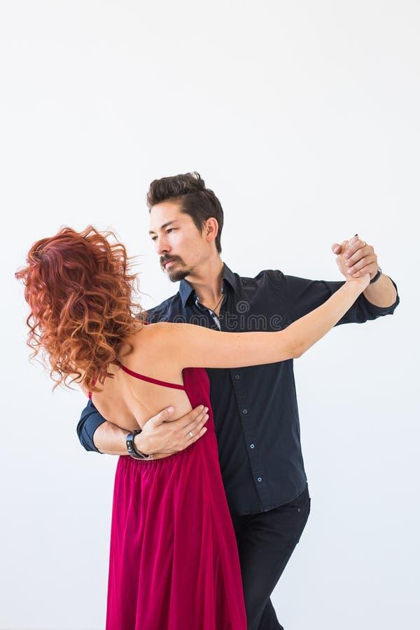 Social dans, bachata, kizomba, folkbegrepp - ung nätt kvinna i rosa klänning- och mandansvals eller salsa arkivbilder