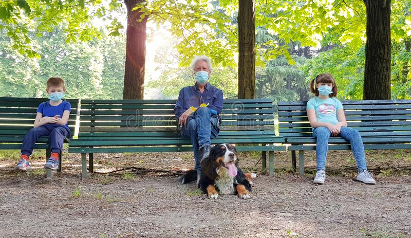 Social distancing: grandfather and grandchildren are sitting on park benches with masks during the coronavirus pandemic royalty free stock photos