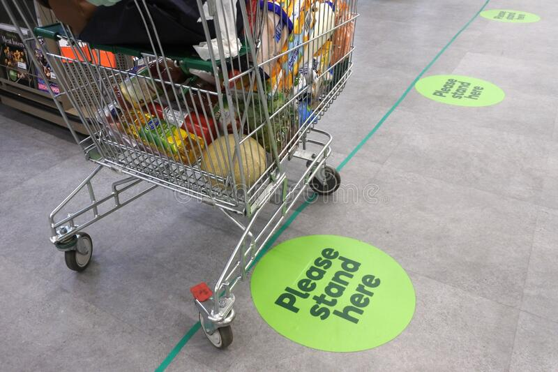 Social distancing marks on supermarket floor intended to stop or slow down the spread of a contagious Coronavirus COVID-19. Social distancing marks on stock photography