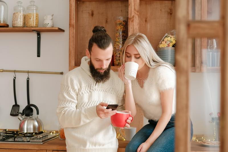 Social media addiction couple kitchen smartphone. Social media addiction. Couple drinking coffee in kitchen, using smartphone to check news feed and posts royalty free stock images