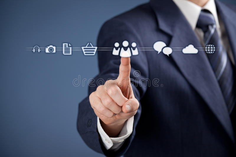 Social media concept. Businessman click on virtual icon representing social media. Horizontal composition, blue background, selective focused on hand