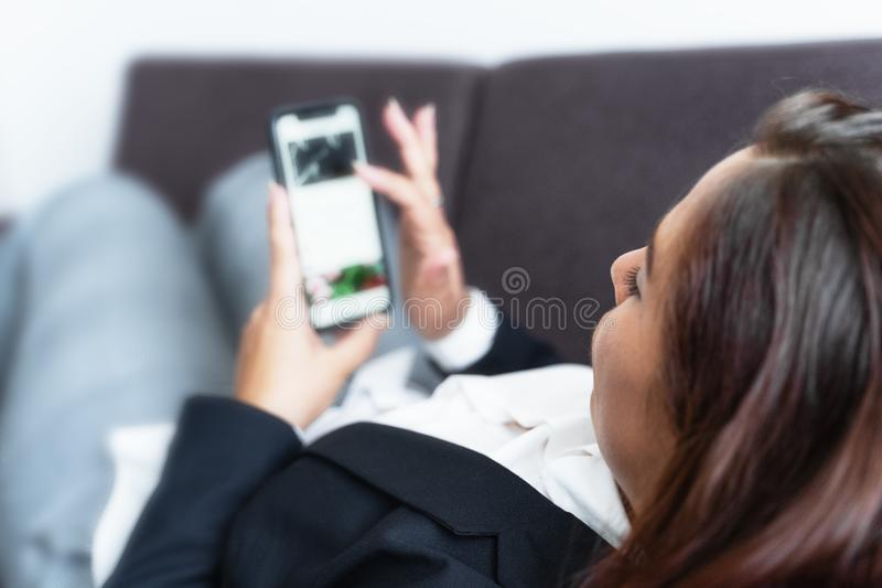 Social media concept, young woman uses smart phone lying on sofa, browsing internet or writing message stock images