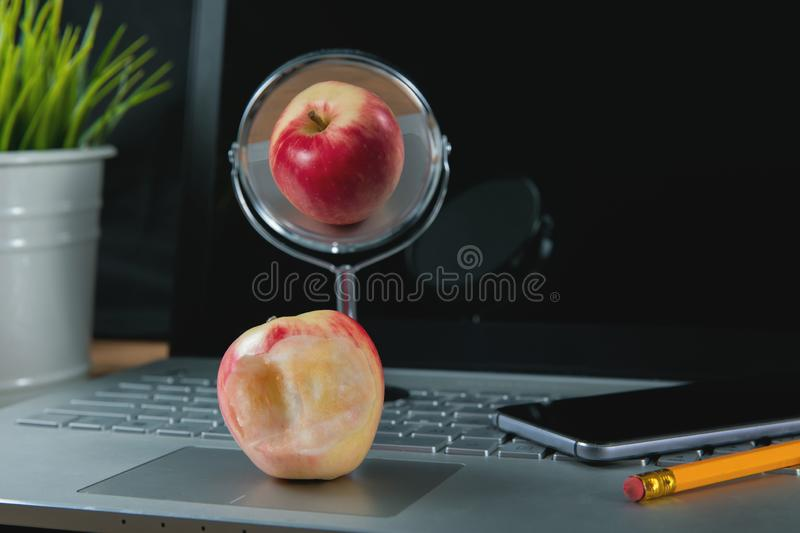 Social media fakeness and cheating concept. Bitten apple with perfect reflection royalty free stock photography