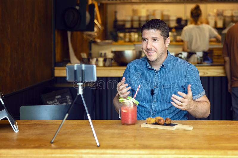 Social media influencer or food blogger filming video sharing online food review of new small restaurant business. Social media influencer or food blogger royalty free stock images