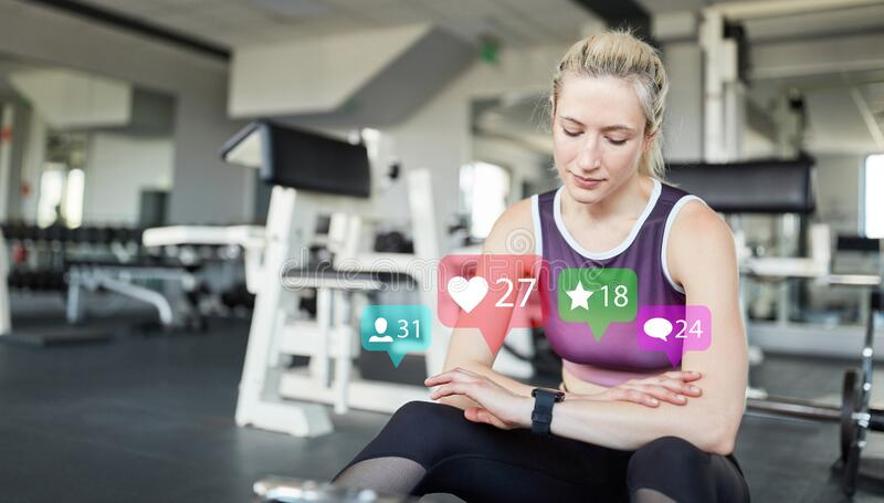 Social media influencer with smartwatch in the fitness center. Young woman as social media influencer with smartwatch in fitness center royalty free stock photography