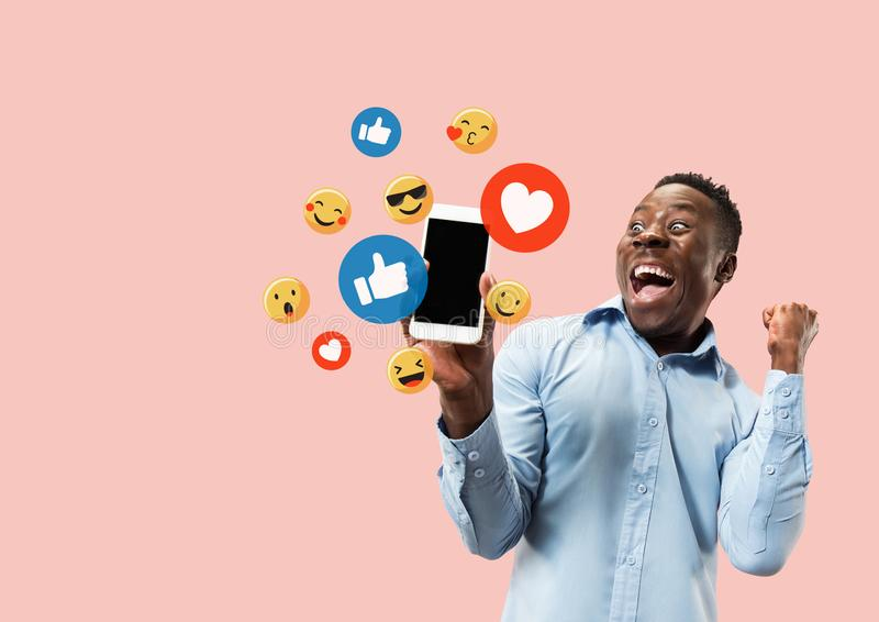 Social media interactions on mobile phone. Internet digital marketing, Chating, commenting, liking. Smiles and icons above smartphone screen, that holding by stock image