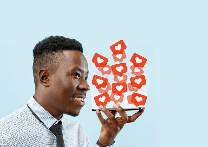 Social media interactions on mobile phone. Internet digital marketing, Chating, commenting, liking. Smiles and icons above smartphone screen, that holding by royalty free stock images