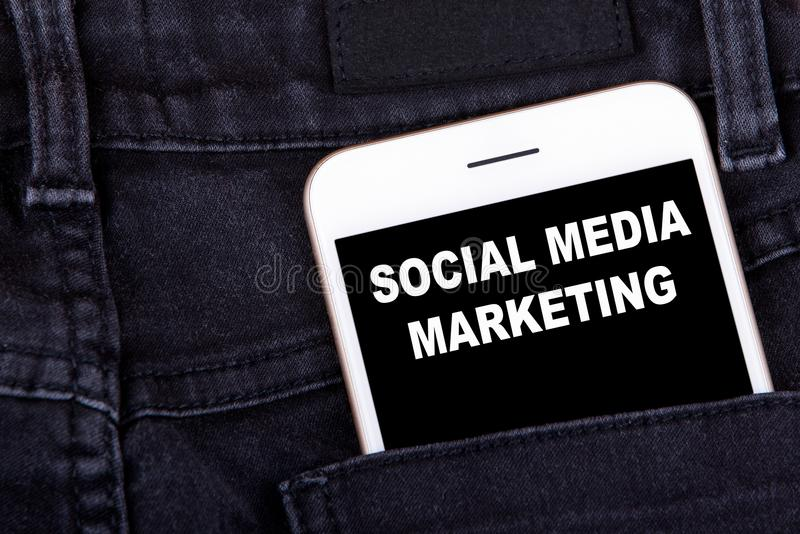 Social media marketing. Smartphone in jeans pocket. Technology business and advertising campaign development background royalty free stock photo