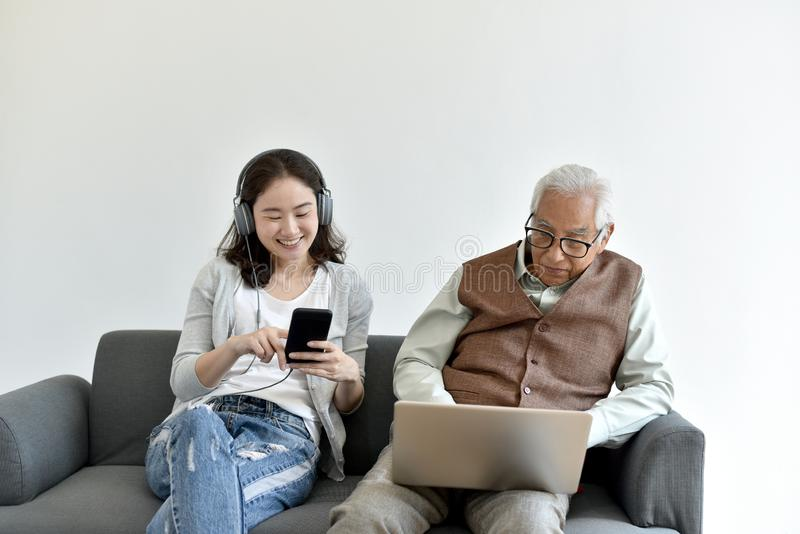 Social media network addiction, Family relationship conflict, Senior asian old father and daughter busy with their smartphone. stock photos