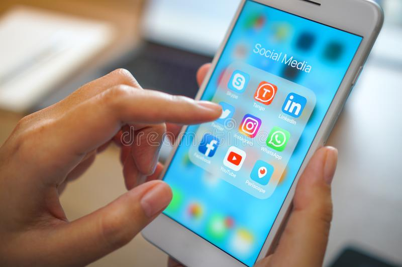 Social medial app iPhone mobile phone with blue screen background technology business smartphone digital communication facebook. Bangkok, Thailand - JUN 18, 2018 stock photography