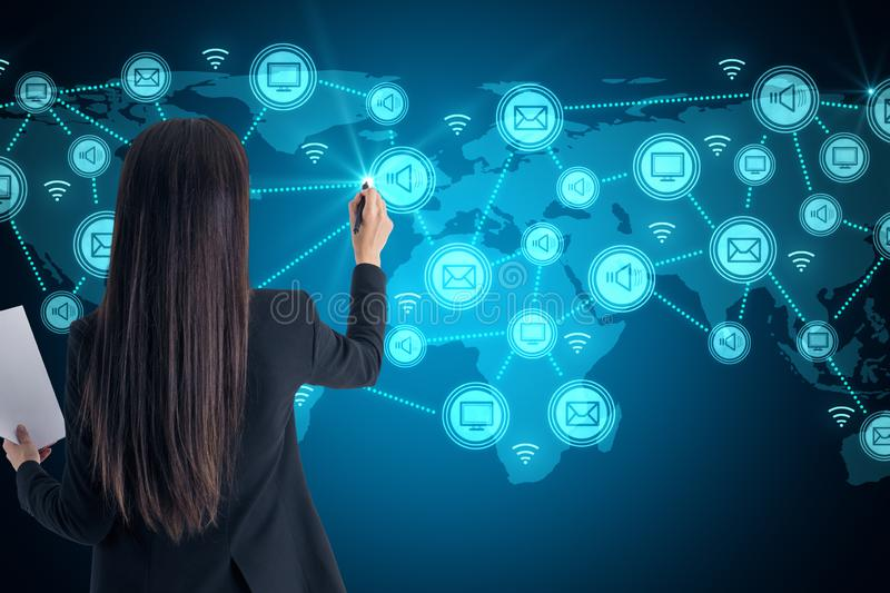 Social network and communication concept. Attractive young businesswoman with document using glowing connections on blue digital map stock photo