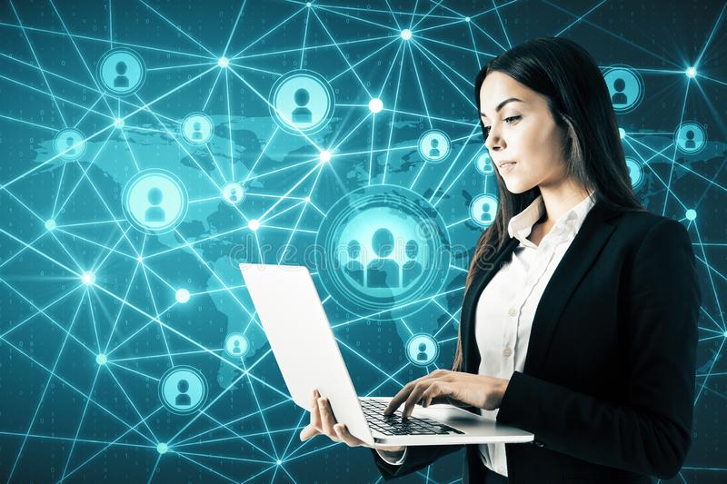 Social network and communication concept. Attractive young businesswoman with laptop using glowing connections on blue digital map stock photos