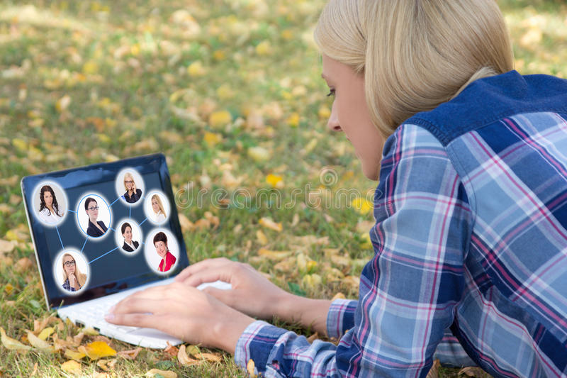 Social network concept - woman using laptop with people portrait royalty free stock photos