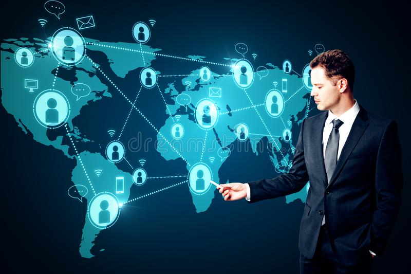 Social network and future concept. Attractive young businessman using glowing map with connections. Social network and future concept royalty free stock photos