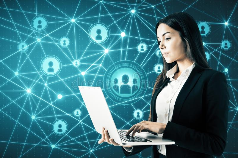 Social network and future concept. Attractive young businesswoman with laptop using glowing connections on blue digital map stock images