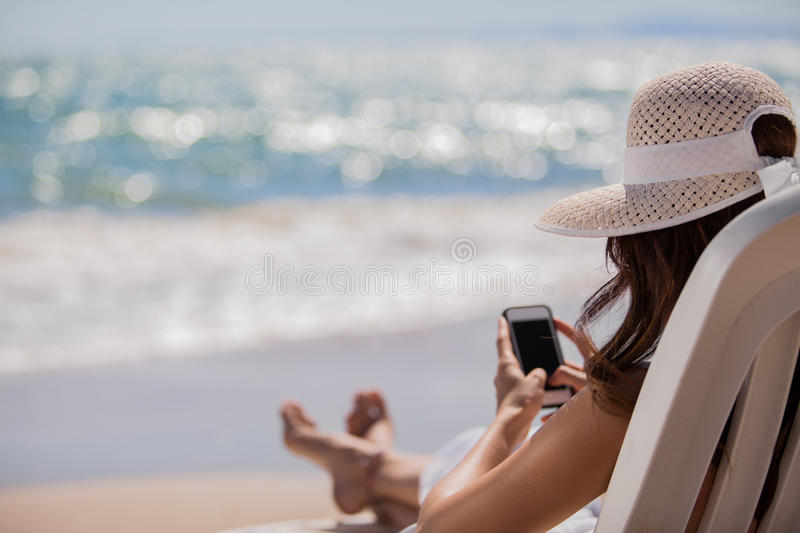 Social networking at the beach. Young woman updating her social network status while relaxing at the beach royalty free stock photos
