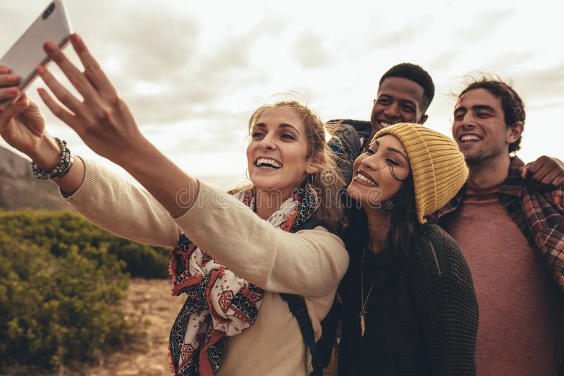 Group selfie on hiking trip. Social networking friends meet up for hiking trip and taking photographs. Group of creative people shooting new content for their royalty free stock photo