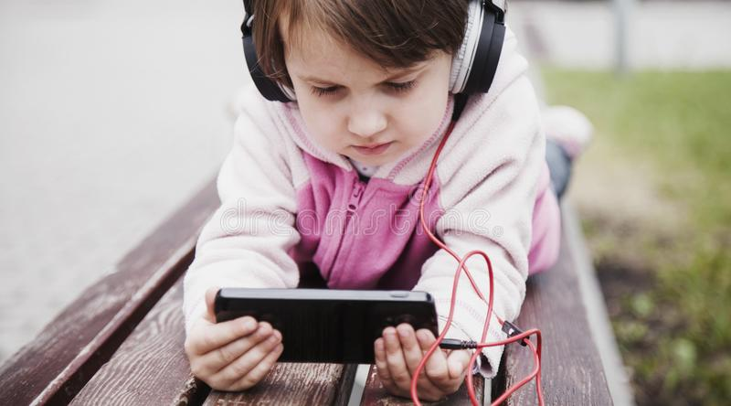 Social networks, friendship, technology and children concept. Portrait of little child girl with phones and headphones royalty free stock photos