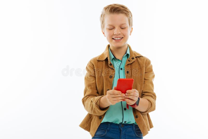 Happy cheerful young boy communicating on the internet. Social networks. Happy cheerful boy writing a message while communicating on the internet stock image