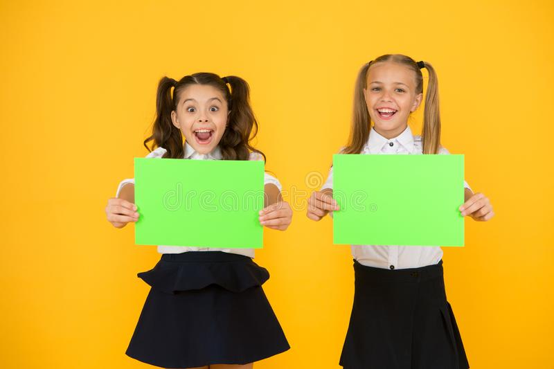 Social poster copy space. Socialization involves how children get along with each other. School socialization. Girls. School uniform hold poster. Back to school royalty free stock photo