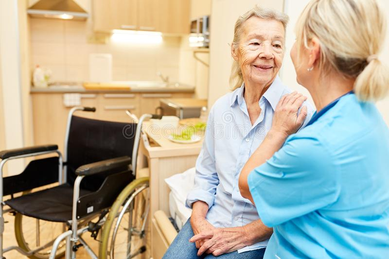 Social service consoles disabled senior woman. Social service consoles disabled senior women in retirement home or nursing home stock image
