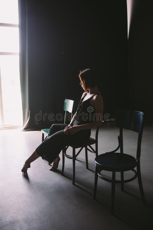 The social theme female loneliness pain suffering. Abastration male violence family. A young beautiful Caucasian woman in black cl. Othes sitting on three chairs stock images