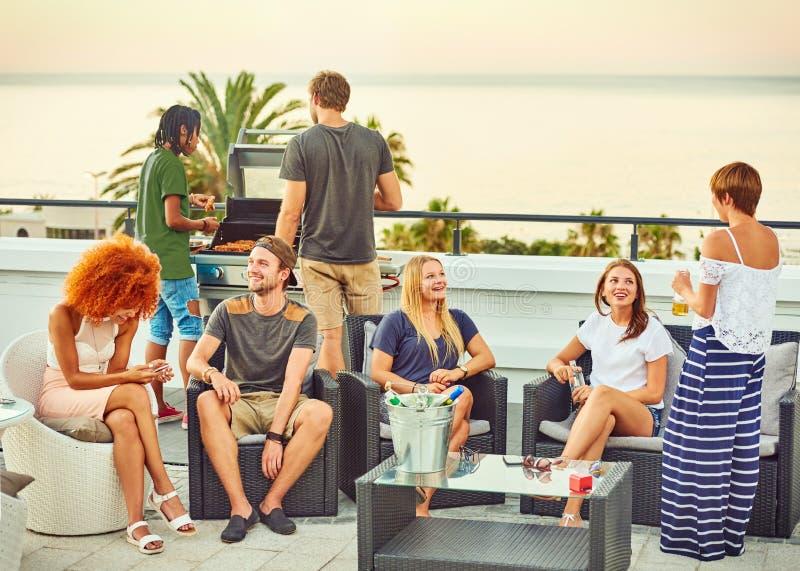 Social växelverkan bland en attraktiv grupp av frineds under grillfest royaltyfri foto