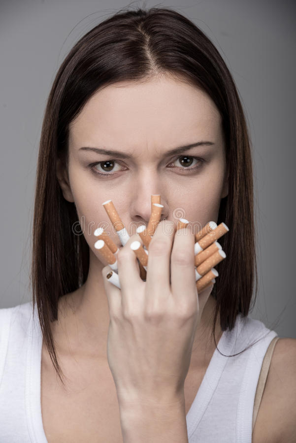 Social. Young woman with many cigarettes. Concept of quit smoking royalty free stock image