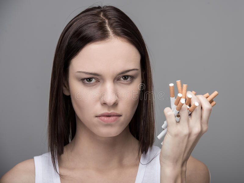 Social. Young woman with many cigarettes. Concept of quit smoking royalty free stock photography