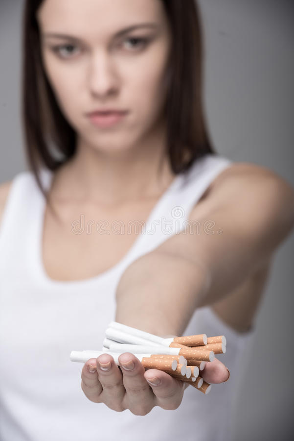 Social. Young woman with many cigarettes. Concept of quit smoking stock photos